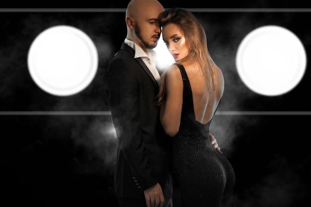 Glamour jeune couple en costumes noirs câlins en studio sur mur noir avec de la fumée