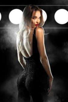 Glamour jeune femme aux lèvres rouges en costume noir serré regardant la caméra en studio sur un mur sombre avec de la fumée et des illuminations