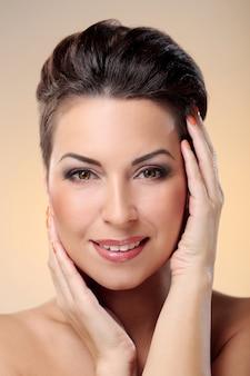 Glamour et magnifique brunette toucher son visage