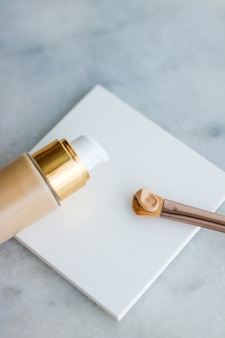 Glamour de marque cosmétique et concept de soins de la peau flacon de fond de teint et pinceau de contour sur la crème anti-cernes de maquillage en marbre comme produit cosmétique pour la conception de vacances de marque de beauté de luxe