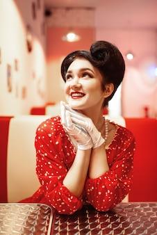 Glamour pin up girl avec des lèvres rouges assis dans un café rétro, 50 mode américaine. robe à pois, style vintage