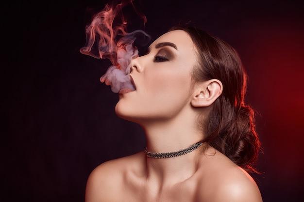 Glamour séduisante superbe femme brune fumer une cigarette électronique
