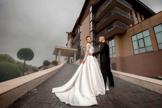 Glamrou jeune couple joyeux posant à l'extérieur par temps pluvieux