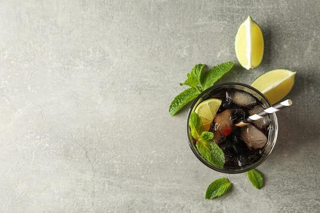 Glasse avec cola froid et agrumes sur table grise, vue du dessus