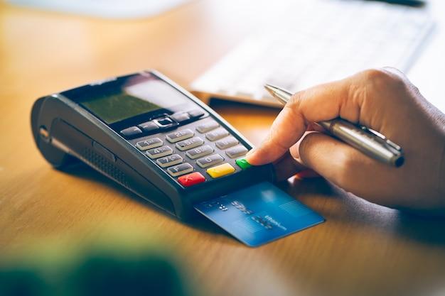 Glissement de votre carte de crédit dans le terminal pour vente ou achat
