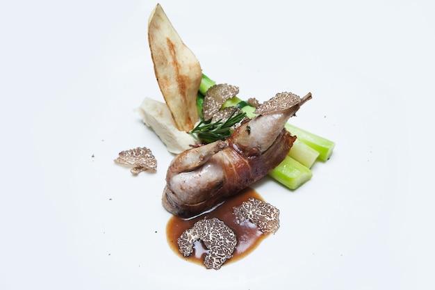 Glisser les champignons truffes sur les aliments dans une assiette blanche.