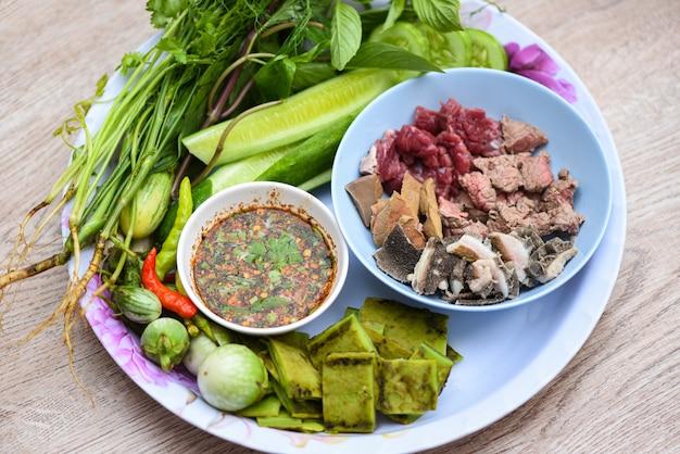 Glissière de boeuf à la viande crue avec sauce épicée et légumes frais sur plateau cuisine thaïlandaise asiatique