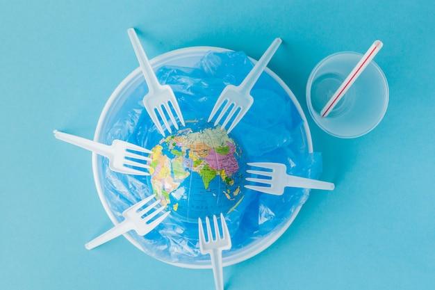 Globe sur une assiette en plastique sur fond bleu