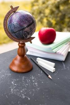 Globe avec cahiers et pomme sur le tableau noir.