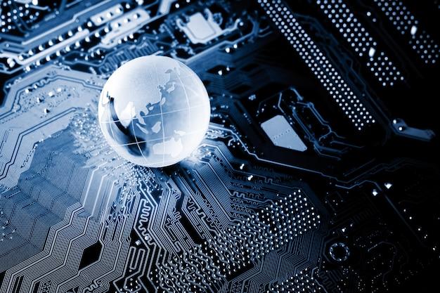 Globe de cristal bleu étincelant sur une carte de circuit informatique dans le noir.