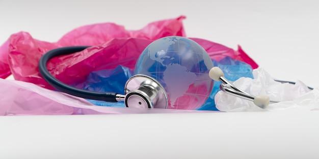 Globe en cristal et stéthoscope sur sac en plastique. les déchets plastiques débordent du monde