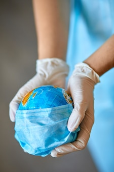 Globe dans un masque médical entre les mains du médecin