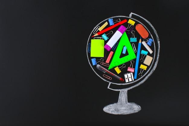 Globe dessiné à la craie contenant un tableau noir de fournitures scolaires et de bureau. étude de concept, école, vente.