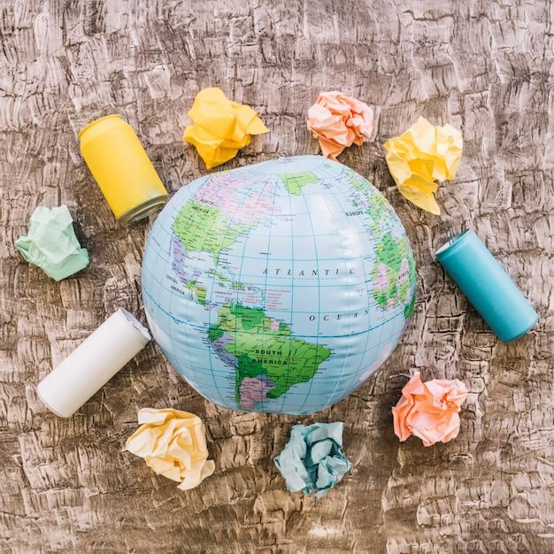 Globe entouré de déchets sur la surface en bois