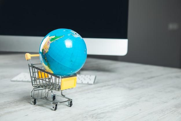 Globe sur le panier et ordinateur sur le bureau