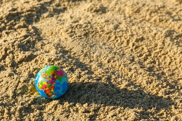 Globe de la planète terre sur une plage de sable fin se bouchent.