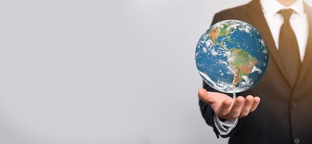 Globe terrestre en 3d chez l'homme, la main de la femme, les mains sur fond bleu. concept de protection de l'environnement. éléments de cette image fournis par la nasa