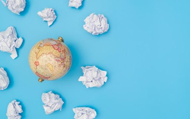 Globe terrestre dans un nuage de papier avec espace de copie bleu