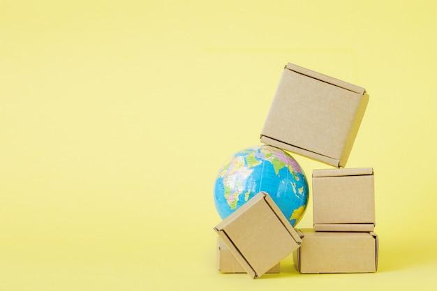Le globe terrestre est entouré de boîtes. commerce mondial et transport international de produits de marchandises. transport maritime, commerce mondial et économie. distribution, import export. chiffre d'affaires des produits.