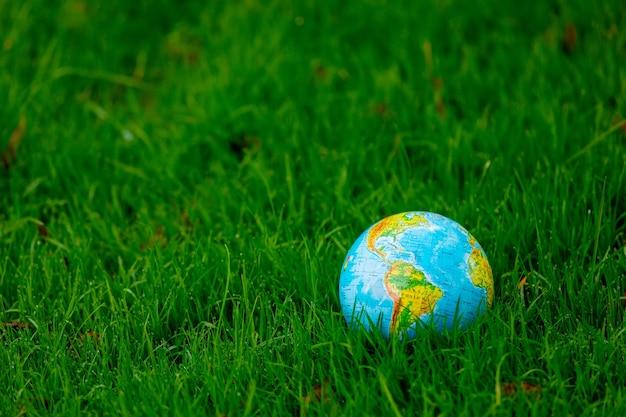 Globe terrestre sur l'herbe verte avec des feuilles d'automne