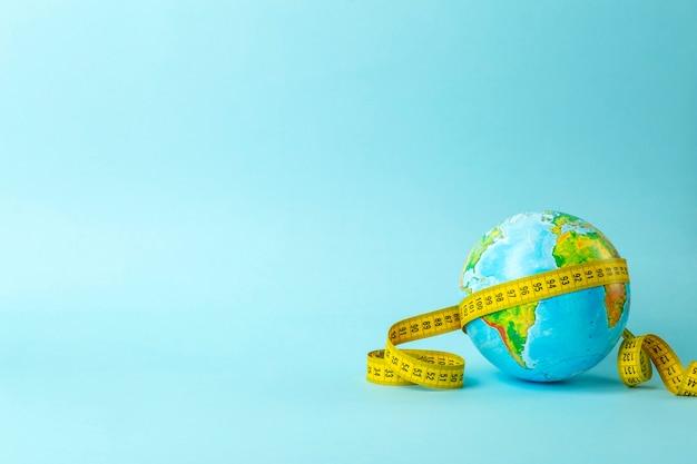 Globe terrestre et ruban à mesurer. espace de copie minimal.