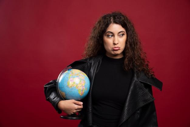 Gloomy woman holding globe.