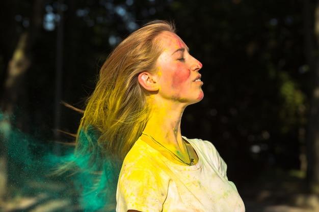 Glorieuse femme blonde jouant avec de la peinture sèche verte holi dans le parc
