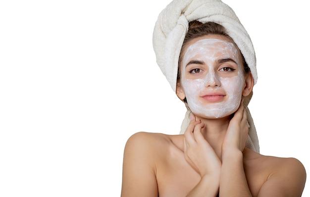 Glorieuse femme brune appliquant un masque crème hydratant et une serviette de bain sur la tête. espace pour le texte