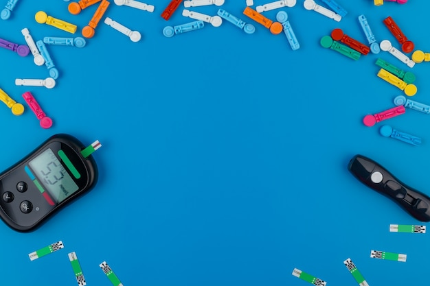 Glucomètre. un appareil pour mesurer la glycémie. bandelettes de test, pilules sur fond bleu.