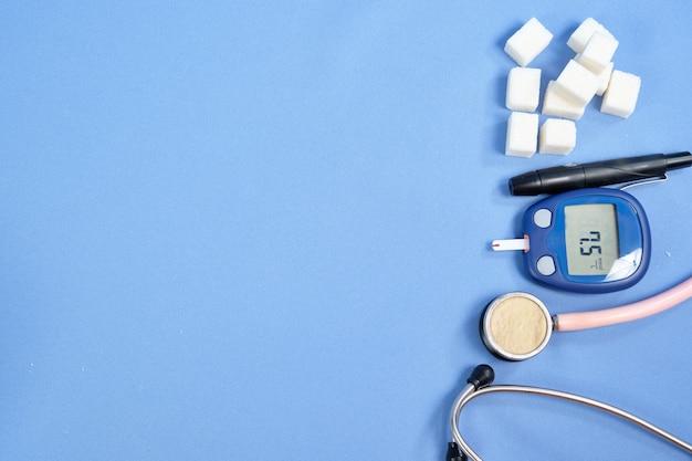 Le glucomètre avec la bandelette de test sur un espace bleu. espace pour le texte