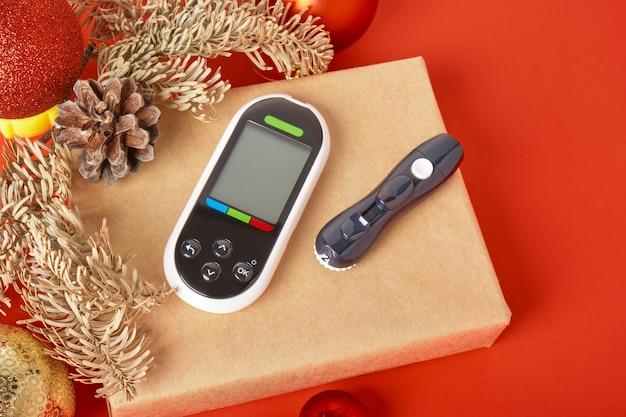 Glucomètre sur une boîte-cadeau, cadeaux de noël et du nouvel an pour les diabétiques, glucomètre en cadeau, espace de copie sur fond rouge