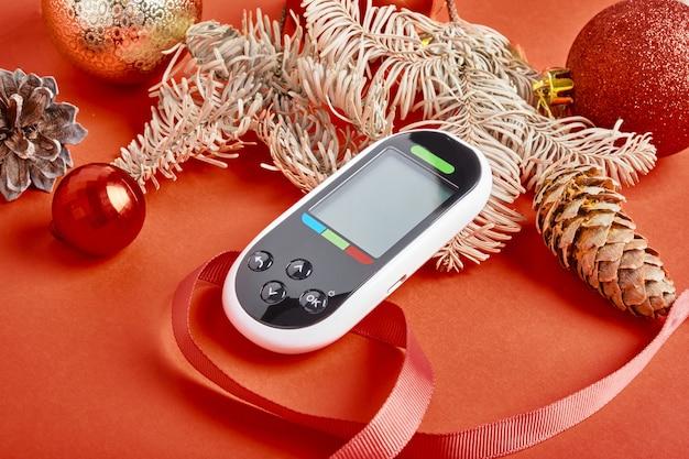Glucomètre décorations de noël et du nouvel an, concept de diabète et de vacances, glucomètre en cadeau, espace de copie de fond rouge