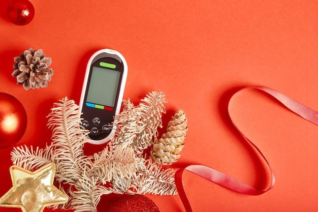 Glucomètre décorations de noël et du nouvel an, concept de diabète et de vacances, glucomètre en cadeau, vue de dessus de l'espace de copie de fond rouge