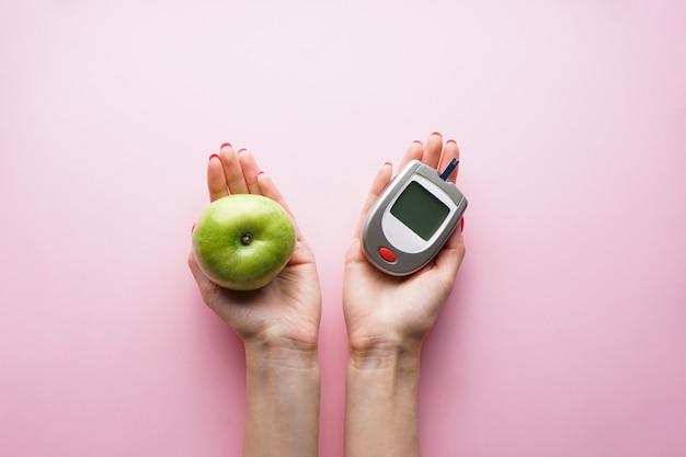 Glucomètre numérique et fruits en mains