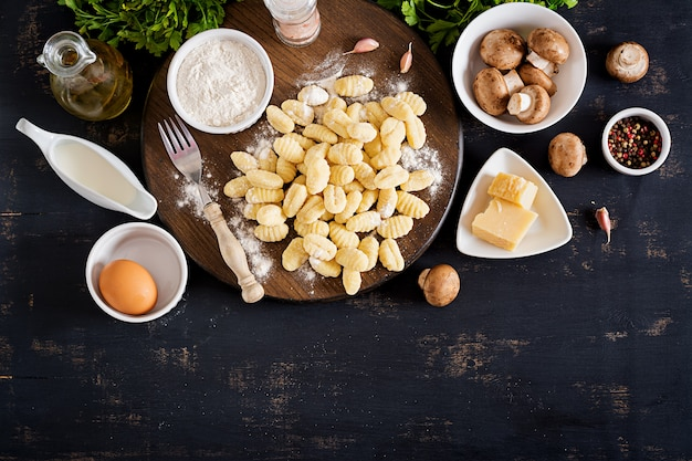 Gnocchi maison non cuit avec une sauce à la crème aux champignons et au persil dans un bol