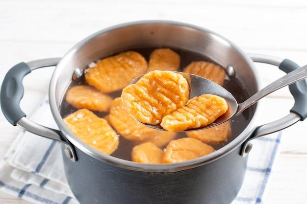 Gnocchi en préparation. ébullition. boulettes de pâte à la citrouille, nourriture végétalienne
