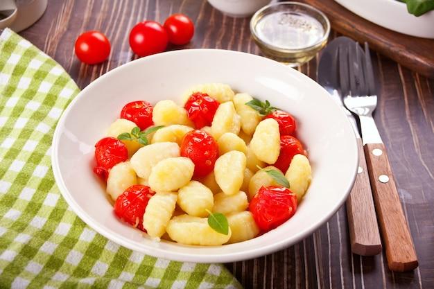 Gnocchis italiens faits maison avec cerise de tomate sur la table en bois