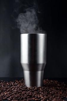 Gobelet en acier inoxydable de café noir chaud sur tas de graines de café sur fond noir. café noir chaud et vapeur. fermer.