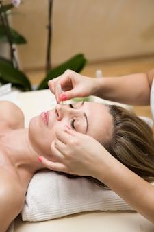 Gobelet appliqué sur la peau du visage d'une patiente dans le cadre de la méthode traditionnelle de thérapie par ventouses