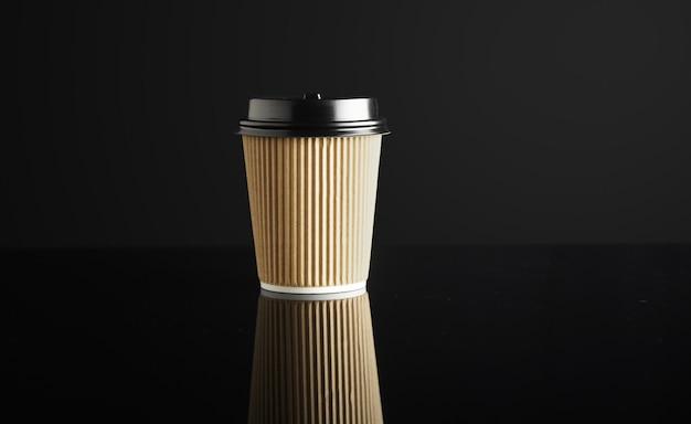 Un gobelet en carton à emporter fermé avec des bouchons isolés sur fond noir et en miroir. présentation au détail