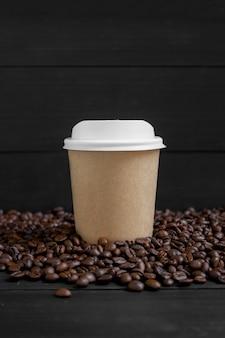 Gobelet en papier et grain de café sur bois noir
