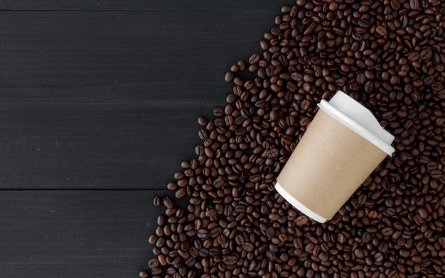 Gobelet en papier et grain de café sur fond de bois noir. vue de dessus