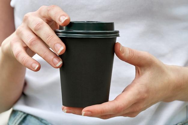 Gobelet en papier noir gros plan avec du café dans les mains de la femme. maquette