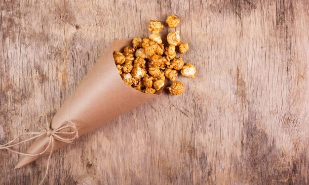 Gobelet en papier avec pop-corn au caramel sur fond en bois, espace copie.