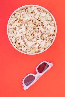 Gobelet en papier avec pop-corn et lunettes 3d sur fond rouge, vue de dessus. mise à plat. copyspace.