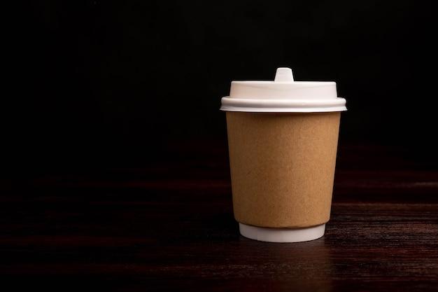 Gobelet en papier pour boissons chaudes isolé sur une table en bois sur fond noir.