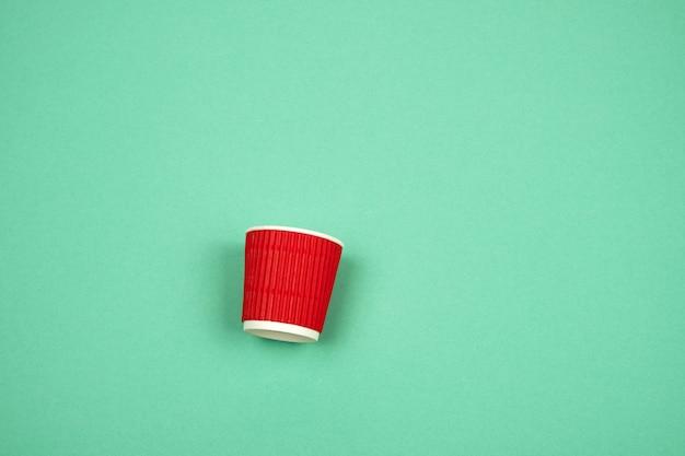Gobelet en papier rouge avec bords ondulés pour boissons chaudes sur vert
