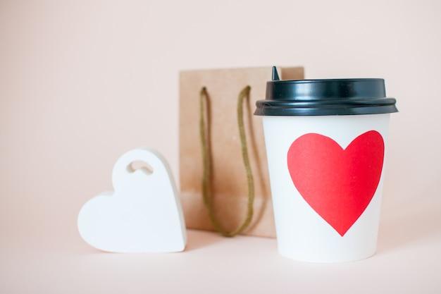 Gobelet en papier, sac cadeau en papier et figurine coeur. la saint-valentin