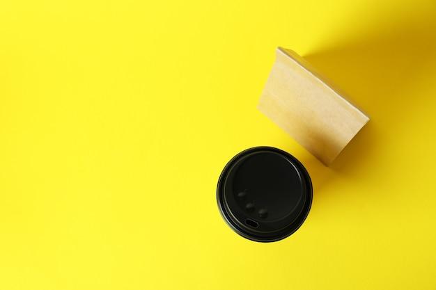Gobelet en papier et sac en papier sur fond jaune