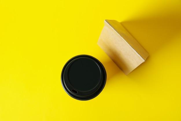 Gobelet En Papier Et Sac En Papier Sur Une Surface Jaune Photo Premium